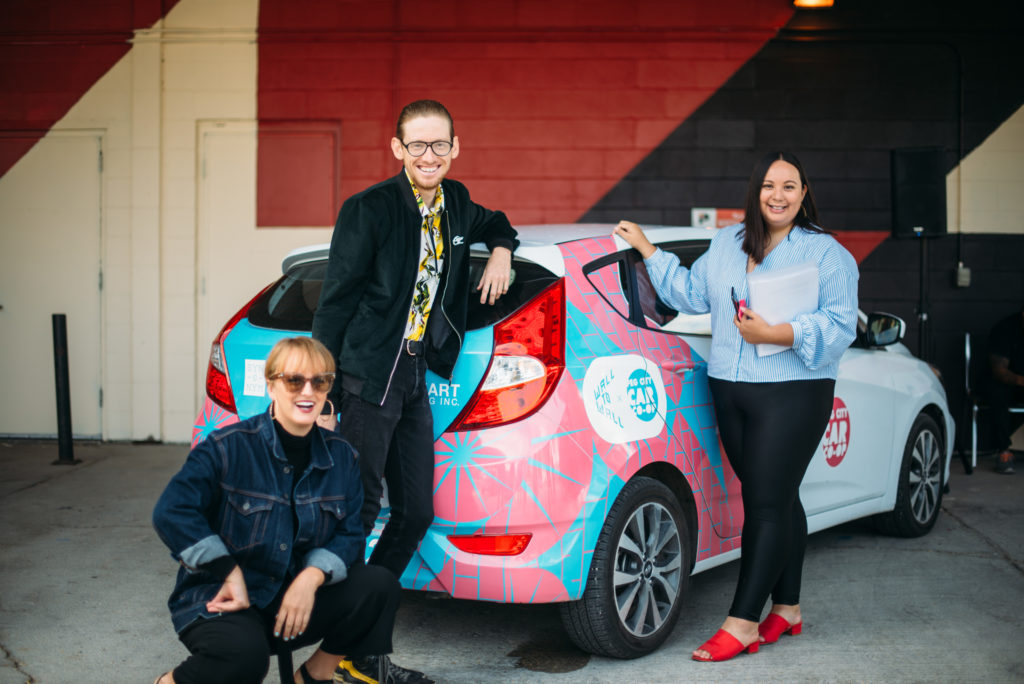 synonym team standing near Peg City Car Co-op Image Wrapped vehicle