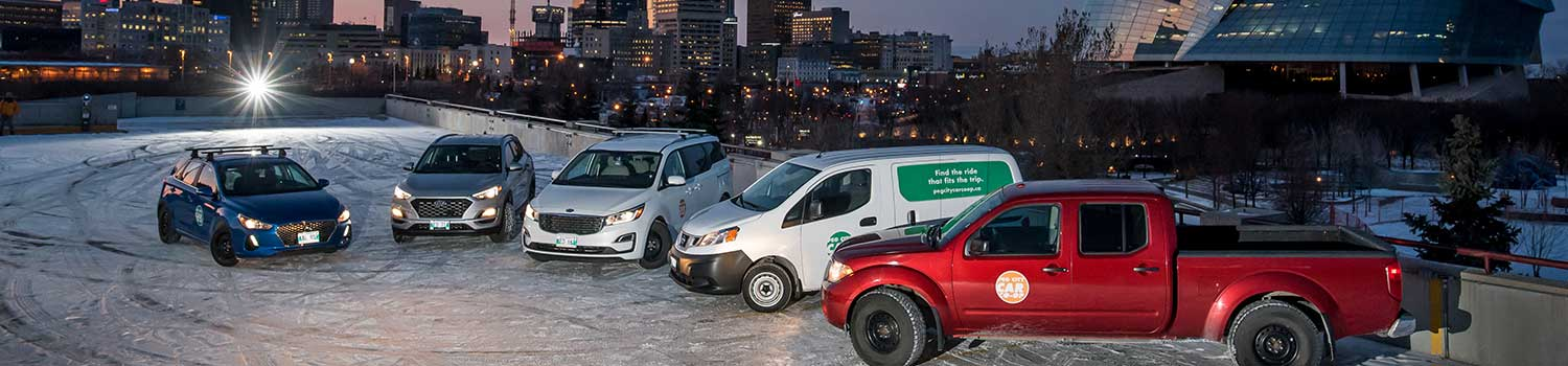various styles of peg city vehicles next to one another in front of the Provencher Bridge in Winnipeg