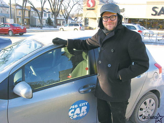 Man standing near Peg City Car Co-op Car. Aaron Russin, likely starting a car battery during the winter