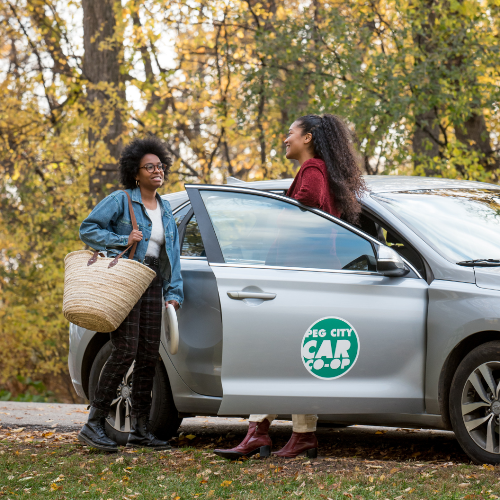 friends talking in the park by Peg City Car Co-op vehicle